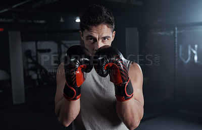 Buy stock photo Portrait of a young man practicing his boxing routine at a gym