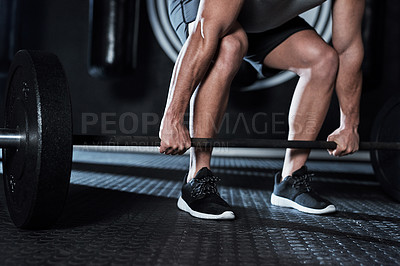 Buy stock photo Shot of an unrecognisable man lifting a barbell during his workout at a gym