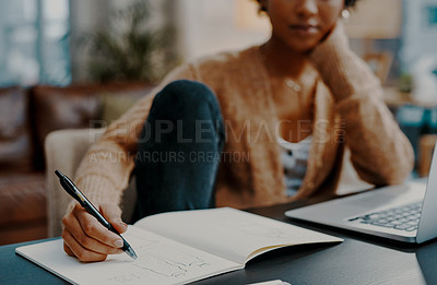 Buy stock photo Closeup shot of a young woman writing notes while working on a laptop at home