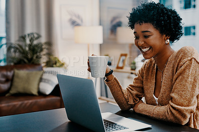 Buy stock photo Shot of a young woman drinking coffee while using a laptop at home