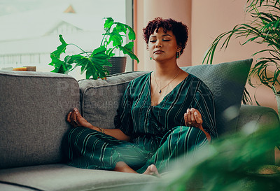 Buy stock photo Shot of a beautiful young woman meditating while sitting on the couch at home