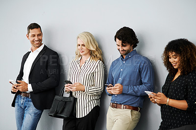 Buy stock photo Shot of a group of businesspeople using their smartphones while waiting in line