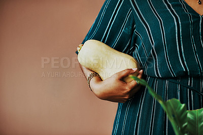 Buy stock photo Cropped shot of an unrecognisable woman holding a butternut on top of her head at home