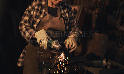 Buy stock photo Shot of a woman using an angle grinder while working at a foundry
