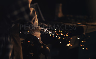 Buy stock photo Shot of a blacksmith using an angle grinder while working at a foundry