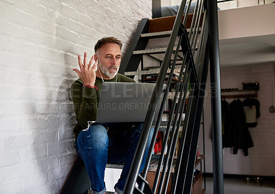 Buy stock photo Shot of a man wearing earphones while using his laptop at home