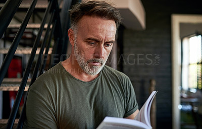 Buy stock photo Cropped shot of a mature man reading a book while sitting at home