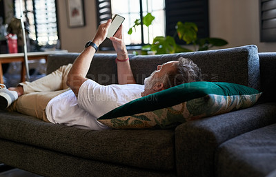 Buy stock photo Shot of a man using his cellphone while lying on the couch at home