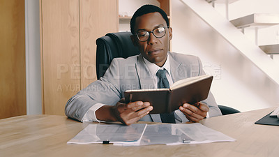 Buy stock photo Shot of a businessman reading through his diary while sitting at his desk