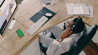 Buy stock photo Shot of a businessman wearing headphones while sitting at his desk