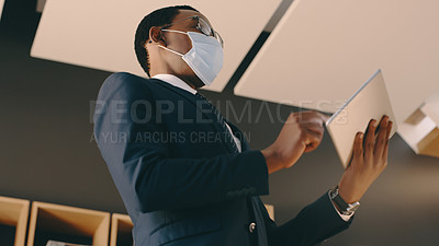 Buy stock photo Shot of a businessman wearing a mask and using a digital tablet in his office