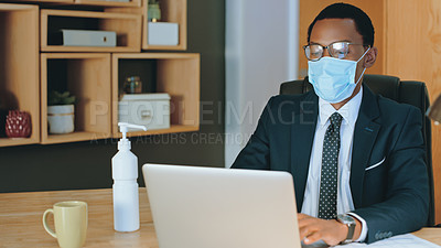 Buy stock photo Shot of a businessman wearing a mask and working on his laptop in an office