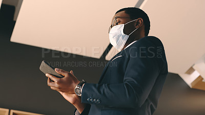 Buy stock photo Shot of a businessman wearing a mask and using his cellphone in an office