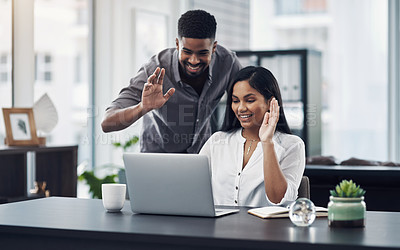 Buy stock photo Shot of two businesspeople making a video call on a laptop in an office