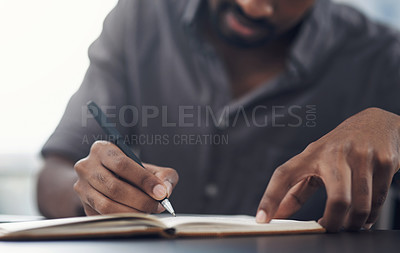 Buy stock photo Closeup shot of an unrecognisable businessman writing in a notebook in an office