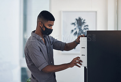Buy stock photo Shot of a young businessman wearing a face mask while standing at a filling cabinet in an office
