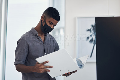 Buy stock photo Shot of a young businessman wearing a face mask while going through a folder in an office
