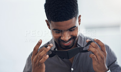 Buy stock photo Shot of a young businessman putting on a face mask in an office