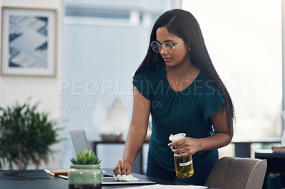 Buy stock photo Shot of a young businesswoman cleaning a laptop in an office