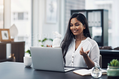 Buy stock photo Shot of a young businesswoman making a video call on a laptop in an office