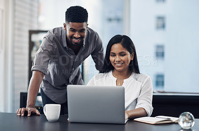 Buy stock photo Shot of two businesspeople working together on a laptop in an office