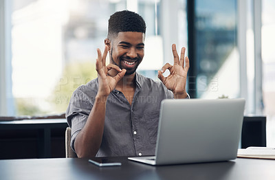 Buy stock photo Shot of a young businessman making an okay sign during a video call on a laptop in an office
