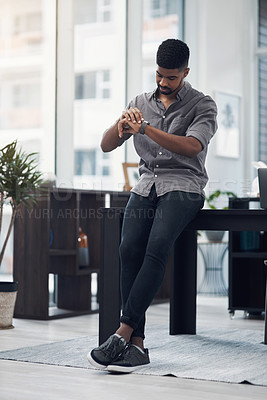 Buy stock photo Shot of a young businessman checking the time on his wristwatch in an office