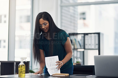 Buy stock photo Shot of a young businesswoman cleaning a workspace in an office