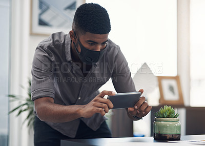 Buy stock photo Shot of a young designer taking photos of his work in an office