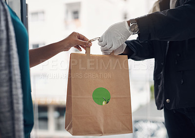 Buy stock photo Shot of an unrecognisable man wearing gloves while delivering takeout to a customer at home