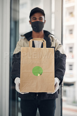 Buy stock photo Shot of a masked young man delivering takeout to a place of residence