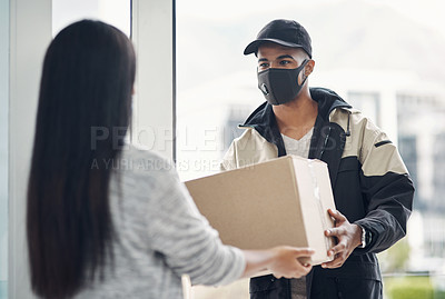 Buy stock photo Shot of a masked young woman receiving a delivery at home
