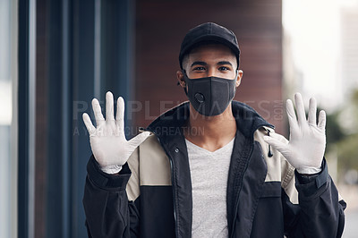 Buy stock photo Shot of a masked young man gesturing with his gloved hands while making a home delivery
