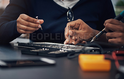 Buy stock photo Shot of two technicians repairing a laptop together