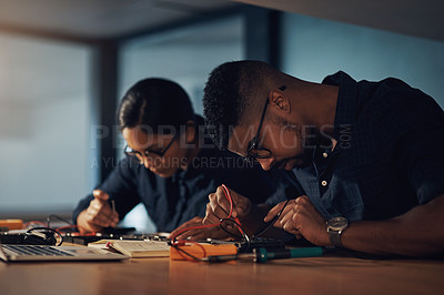 Buy stock photo Shot of two young technicians repairing computer hardware together