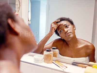 Buy stock photo Cropped shot of a woman looking at her skin in the bathroom mirror