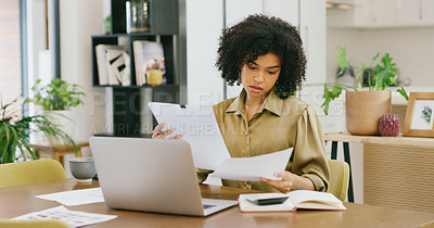 Buy stock photo Shot of a young woman going through paperwork while working on a laptop at home