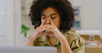 Buy stock photo Shot of a young woman looking stressed out while working on a laptop at home