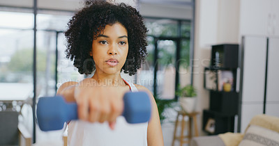 Buy stock photo Shot of a young woman exercising with dumbbells at home