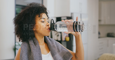 Buy stock photo Shot of a young woman drinking water while exercising at home