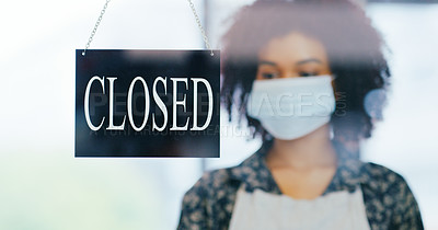 Buy stock photo Shot of a young woman wearing a mask and hanging a close sign on the window of her store