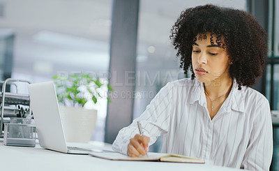 Buy stock photo Shot of young businesswoman writing in a notebook and using a laptop in a modern office