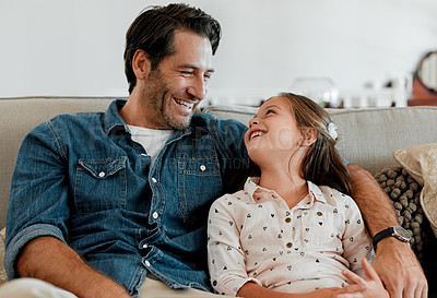 Buy stock photo Shot of a man and his daughter sitting together on the couch at home
