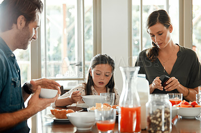 Buy stock photo Shot of a couple and their daughter having breakfast at home