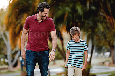 Buy stock photo Shot of a man and his son taking a walk through the park