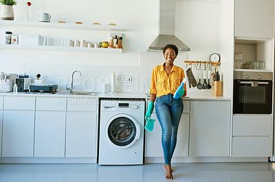 Buy stock photo Portrait of a young woman holding up a cleaning detergent while busy cleaning at home