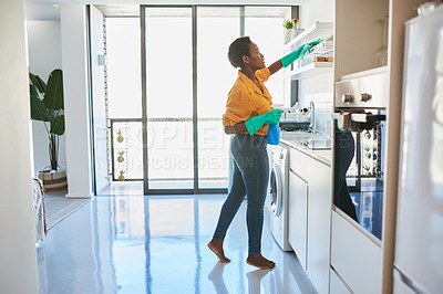 Buy stock photo Shot of a young woman cleaning her home