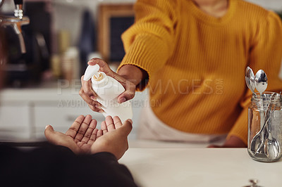 Buy stock photo Cropped shot of a woman sanitising a customer's hands