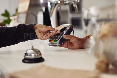 Buy stock photo Cropped shot of a customer tapping her card to make a payment in a cafe