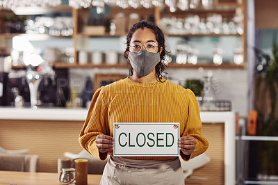 Buy stock photo Shot of a woman wearing a mask and holding up a closed sign in a cafe